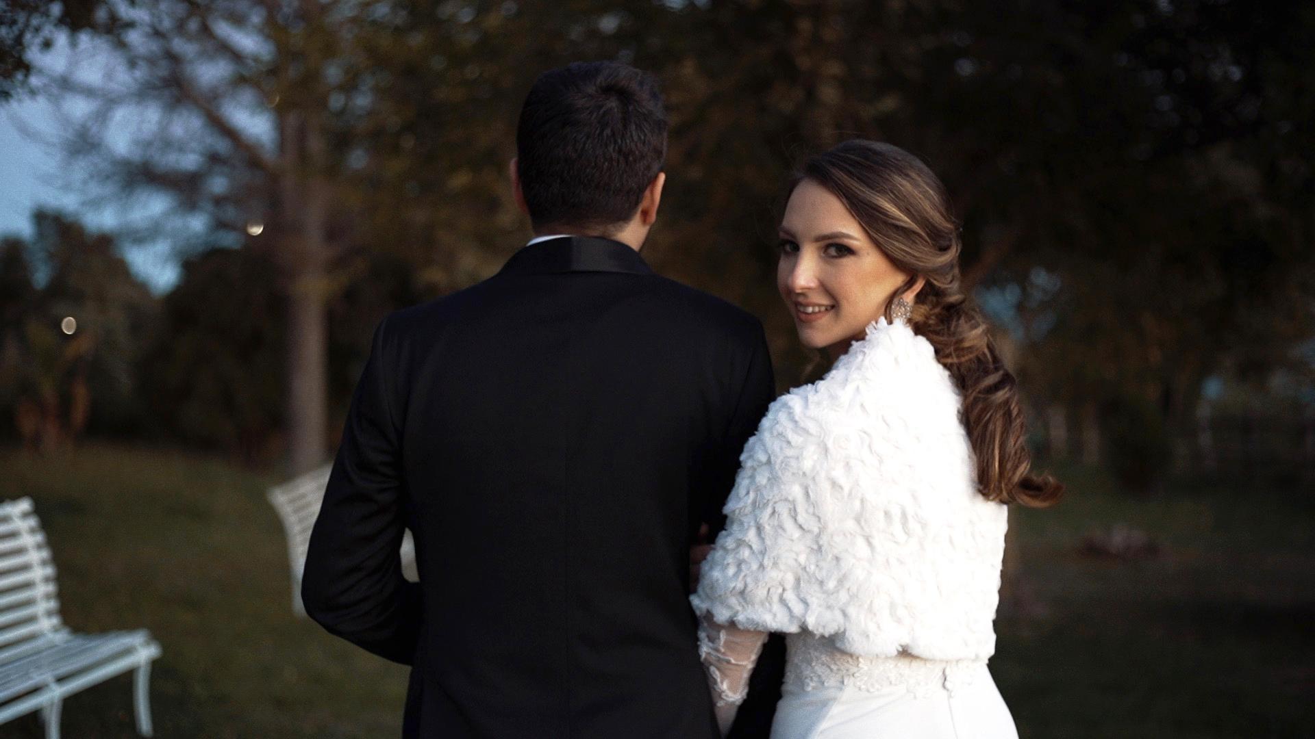 sposa con abito nuziale abbraccia sposo con smoking mentre camminano romanticamente in un giardino verde