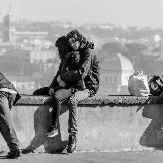 innamorati seduti su un muretto di roma mentre si tengono la mano