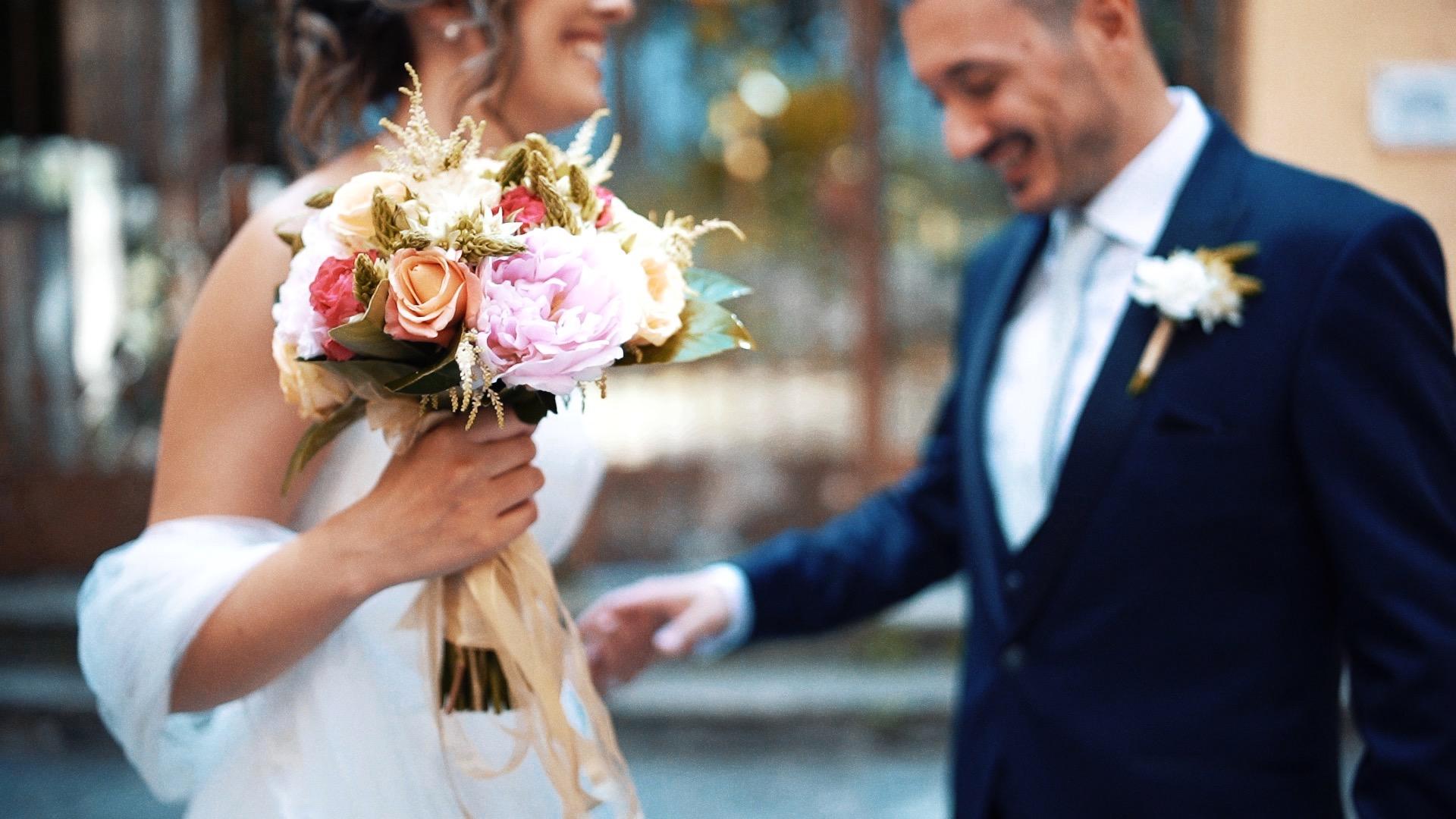 bouquet colorato nelle mani di una sposa mentre incontra per la prima volta il suo futuro marito in abito elegante