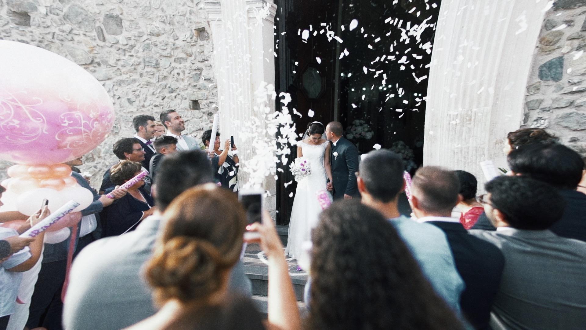sposo e sposa abbracciati escono dal portone della chiesa e vengono inondati dal riso bianco lanciatogli da tutti gli invitati