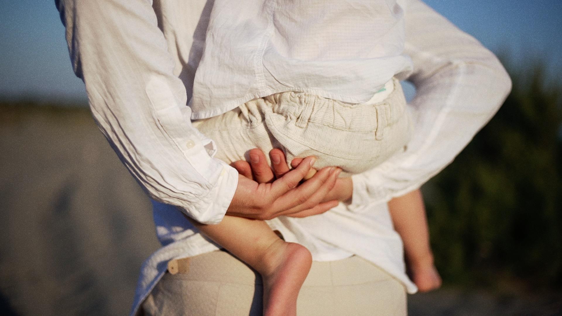Mani sorreggono corpo del bambino sulla schiena