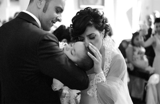 genitori baciano bimbo all'altare